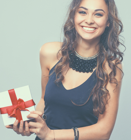 Young woman happy smile hold gift box in hands, isolated over gray