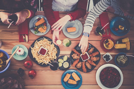 Top view of group of people having dinner together while sitting at wooden table