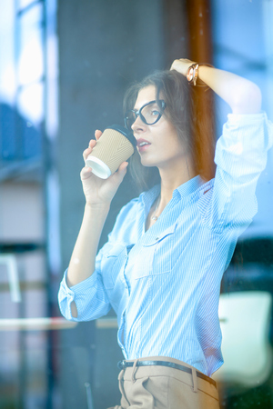 Cheerful businesswoman drinking from mug while working on laptop at the office