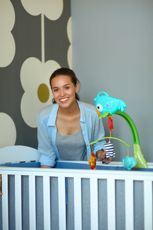 cot: Young woman standing near childrens cot.