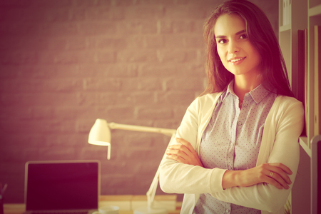 autocad: Young woman standing near desk with laptop