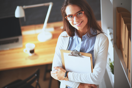 autocad: Young woman standing near desk with laptop holding folder Stock Photo