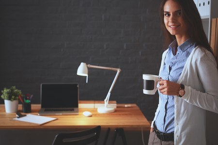 autocad: Young woman standing near desk with laptop holding cup of coffee
