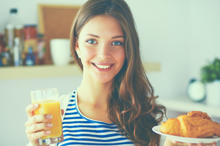 devouring: Young woman with glass of juice and cakes standing in kitchen . Stock Photo