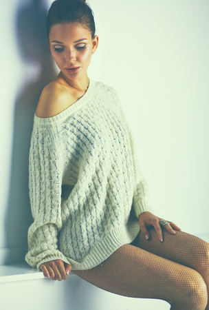 Portrait of a cute woman in sweater at home.