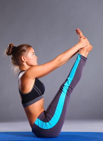 Portrait of sport girl doing yoga stretching exercise.