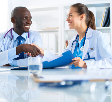 cooperate: Two happy smiling young medical people handshaking at office