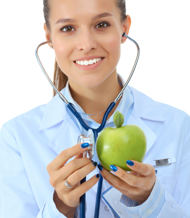 Medical doctor woman examining apple with stethoscope