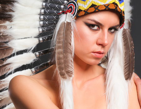 Beautiful woman in native american costume with feathers.