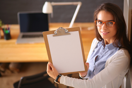 autocad: Young woman standing near desk with laptop holding folder.