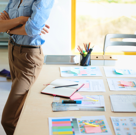 architectural studies: Young female businesswoman in the office near desk. Stock Photo