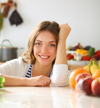 Young woman standing near desk in the kitchen. Stock Photo