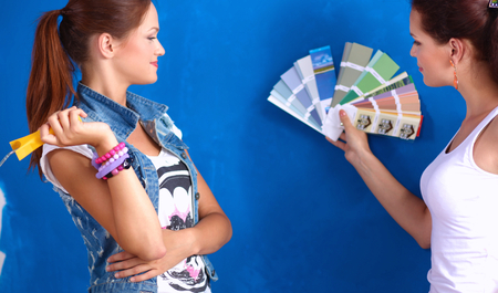 housepainter: Two Beautiful young woman doing wall painting. Stock Photo
