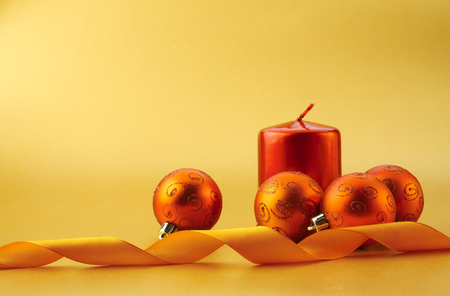 Gold christmas balls and red candle on light background. Stock Photo