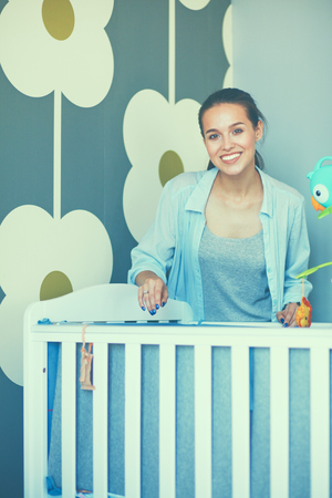 bed skirt: Young smiling woman standing near childrens cot. Stock Photo
