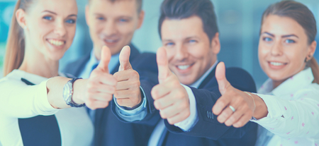 happy business team: Happy business team showing thumbs up in office