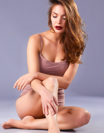 Beautiful barefoot woman sitting on the floor Stock Photo
