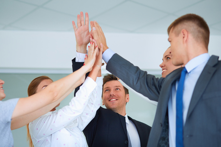 together standing: Business team joining hands together standing in office