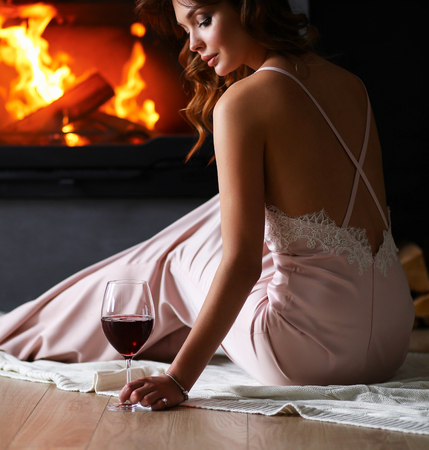 waiting glance: Sexy girl in front of the fireplace Stock Photo