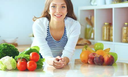 kitchen appliances: Young woman sitting near desk in the kitchen Stock Photo
