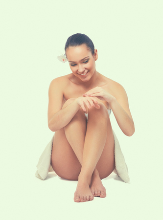 sitting pretty: Female with beautiful legs sitting on the floor in white towel