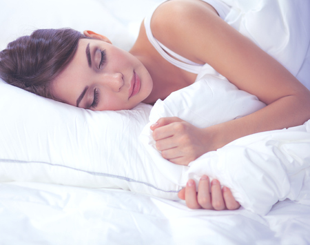 Beautiful girl sleeps in the bedroom, lying on bed Stock Photo