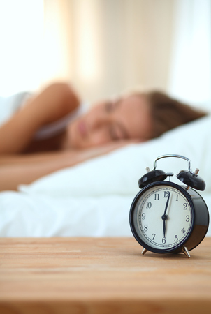 Young Sleeping Woman And Alarm Clock In Bedroom At Home Photo