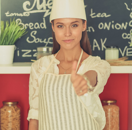 Chef woman portrait with  uniform in the kitchen and showing ok