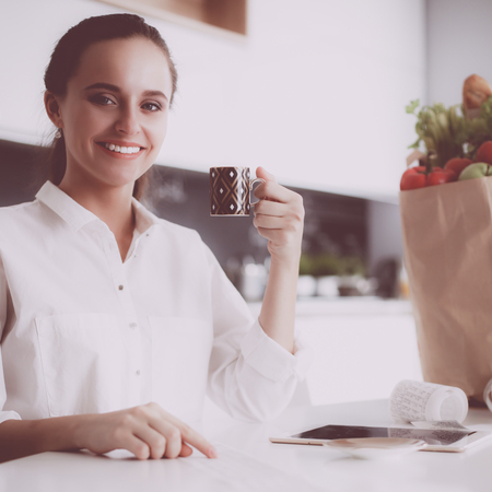 Young woman planning expenses and paying bills on her kitchen Stock Photo