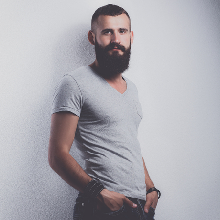 Portrait of handsome bearded man standing, isolated on grey background Stock Photo