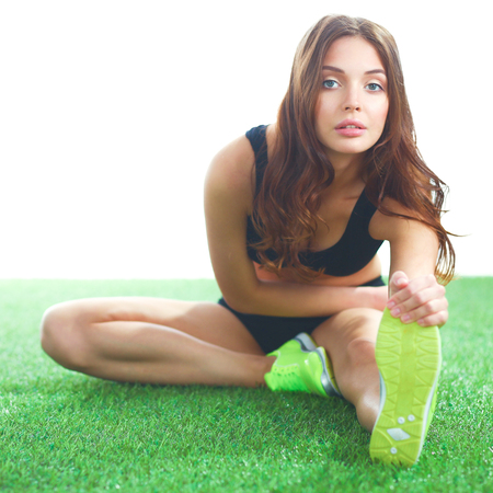 Woman doing stretching exercises on the green grass Stock Photo