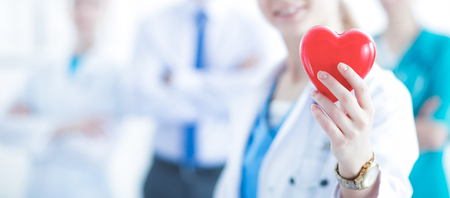 Female doctor with stethoscope holding heart Stock Photo