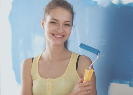 housepainter: Beautiful young woman doing wall painting ,standing Stock Photo