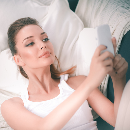 herself: Happy brunette taking a photo of herself with her mobile phone in bedroom