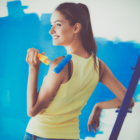 housepainter: Happy beautiful young woman doing wall painting, standing near ladder Stock Photo