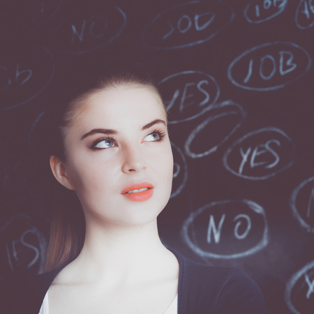 maybe: Young woman is standing on blackboard background and thinking: yes or no.