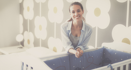 bed skirt: Young beautiful woman standing near children cot Stock Photo