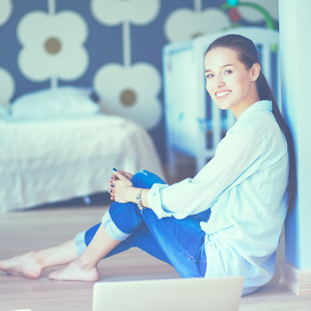 bed skirt: Young woman sitting on the floor near childrens cot Stock Photo