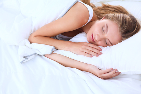 awaking: Young sleeping woman and alarm clock in bedroom at home