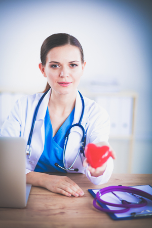 Beautiful young smiling female doctor sitting at the desk and holding heart