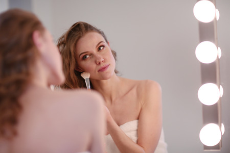 grooming product: Young woman looking in the mirror and putting make-up on