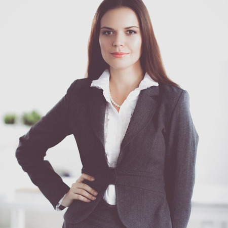 principal: Portrait of business woman standing with crossed arms in office