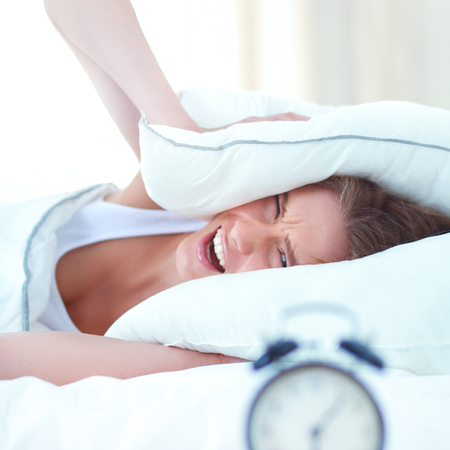 hotel bedroom: Young sleeping woman and alarm clock in bedroom at home