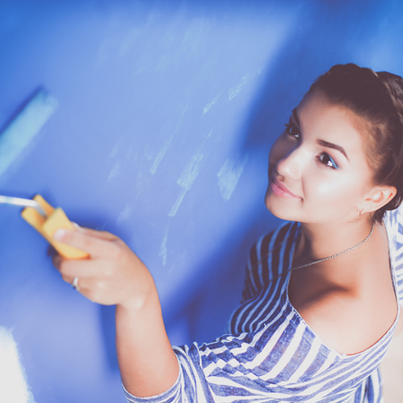 housepainter: Beautiful young woman doing wall painting , standing Stock Photo