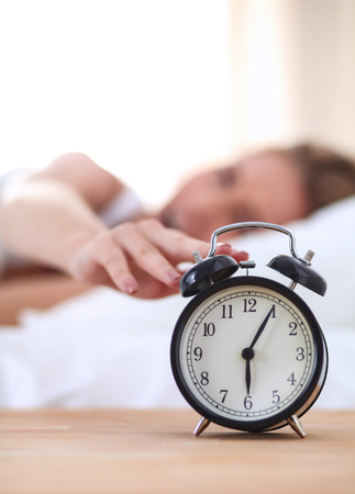 hotel bedroom: Young sleeping woman and alarm clock in bedroom at home.