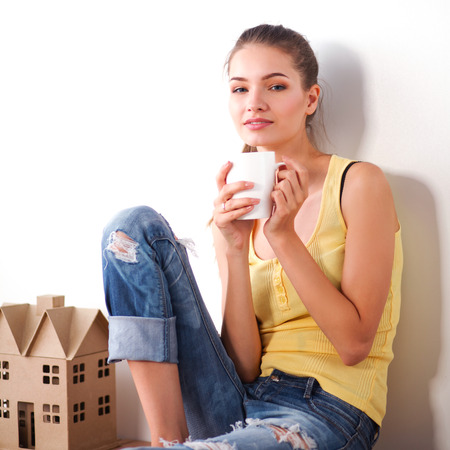 renew.: Portrait of female painter sitting on floor near wall after paintingand holding a cup Stock Photo