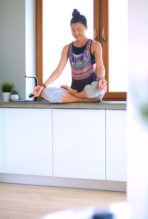 Young beautiful woman sitting at the kitchen table in the lotus position