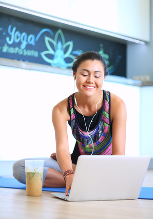 Sporty smiling woman using laptop in bright room
