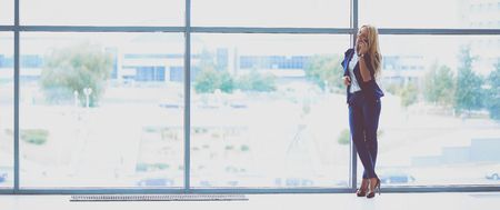 phon: Businesswoman standing against office window talking on mobile phone