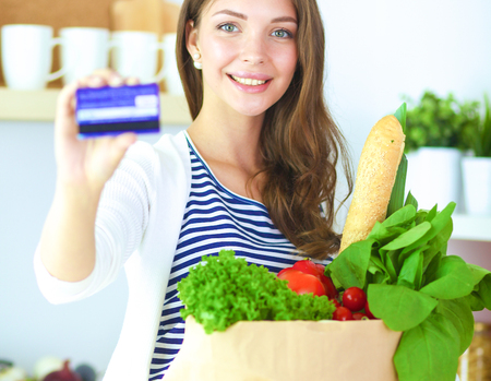 Woman with credit card and shopping bag in the kitchen at home
